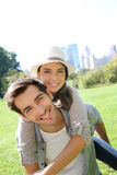 Young couple having fun in central park. Man giving piggyback ride to girlfriend in Central Park Royalty Free Stock Photo