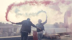 Young couple having fun with colored smoke on the roof of the modern building. Young guy with his girlfriend walking of. Terrace with colored smoke bombs stock footage