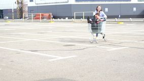 Young couple having fun in a deserted car park stock footage