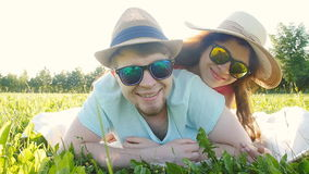Young couple having fun on the grass in a park stock video