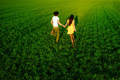 Young couple having fun on the green field in the spring or summ Stock Images