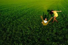 Young couple having fun on the green field in the spring or summ Stock Photos