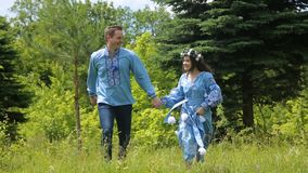 Young couple having fun on the green field in the spring or summer, general plan stock video