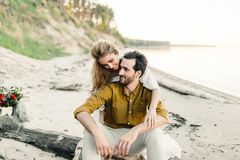 A young couple is having fun and hugging on the beach. Beautiful girl embrace her boyfriend from back. Wedding walk. A Stock Images