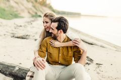 A young couple is having fun and hugging on the beach. Beautiful girl embrace her boyfriend from back. Wedding walk. A Royalty Free Stock Photography