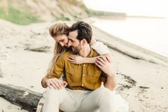 A young couple is having fun and hugging on the beach. Beautiful girl embrace her boyfriend from back. Wedding walk. A Stock Photos