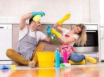 Man and woman happy for finishing chores. Young couple having fun on kitchen floor after finishing chores royalty free stock photography