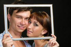 Young couple having fun making faces through frame Royalty Free Stock Photos