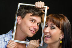 Young couple having fun making faces through frame Royalty Free Stock Images