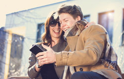 Young couple having fun with mobile phone Royalty Free Stock Photography