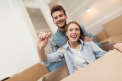 Young couple having fun while moving to new apartment. Moving newlyweds. Girl is sitting in a box. Young couple having fun while moving to new apartment. Moving stock photos