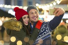 Couple take selfie at Christmas market. Young Couple Having Fun Outdoors At Christmas Time, Europe stock photos