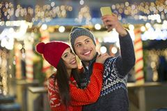 Couple take selfie at Christmas market. Young Couple Having Fun Outdoors At Christmas Time, Europe royalty free stock photo