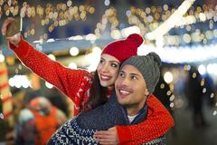 Couple take selfie at Christmas market. Young Couple Having Fun Outdoors At Christmas Time, Europe royalty free stock image