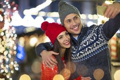 Couple take selfie at Christmas market. Young Couple Having Fun Outdoors At Christmas Time, Europe stock photo