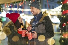 Couple drinking mulled wine at Christmas market. Young Couple Having Fun Outdoors At Christmas Time, Europe royalty free stock photography
