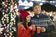 Couple drinking mulled wine at Christmas market. Young Couple Having Fun Outdoors At Christmas Time, Europe royalty free stock image