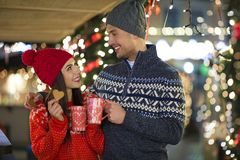 Couple drinking mulled wine at Christmas market. Young Couple Having Fun Outdoors At Christmas Time, Europe royalty free stock photos