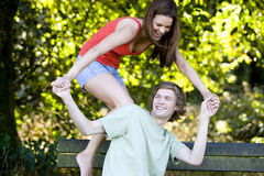 A young couple having fun on a park bench Royalty Free Stock Photo