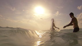Young couple having fun in the sea. Splashing water at sunset stock footage