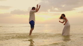 Young couple having fun in the sea. Sprinkle water on each other. At sunset. Slow motion video. Young couple having fun in the sea. Sprinkle water on each other stock footage