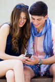 Young couple having fun with smartphones, outdoors Stock Photography