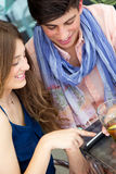 Young couple having fun with smartphones, outdoors Royalty Free Stock Photo