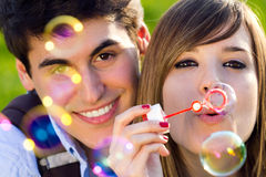 Young couple having fun with soap bubbles in the park Royalty Free Stock Image
