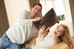 Young couple having fun on sofa Stock Images
