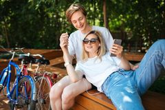 Young couple having fun while spending time in park with two bicycles nearby. Boy sitting on bench in park happily royalty free stock photography