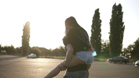 Young couple having fun on summer on an empty parking zone with boyfriend giving piggyback ride to girlfriend. Smiling