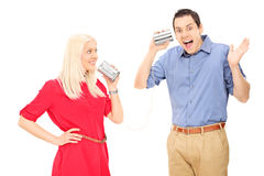 Young couple having fun with a tin can phone Stock Photos