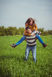 Young couple having fun together in green field. The woman ridin Royalty Free Stock Photos