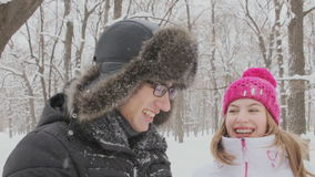 Young couple having fun together in snow in winter woodland throwing snowballs stock video