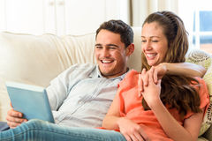 Young couple having fun while using digital tablet on sofa Stock Photos