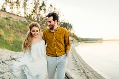 A young couple is having fun and walking on the sea coastline. Newlyweds looking at each other with tenderness. Romantic Royalty Free Stock Images