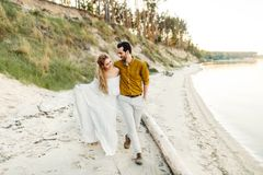 A young couple is having fun and walking on the sea coastline. Newlyweds looking at each other with tenderness. Romantic Royalty Free Stock Photo