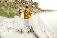 A young couple is having fun and walking on the sea coastline. Newlyweds looking at each other with tenderness. Romantic Royalty Free Stock Photos