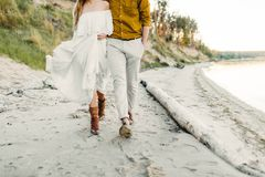 A young couple is having fun and walking on the sea coastline. Newlyweds looking at each other with tenderness. Romantic Royalty Free Stock Photography
