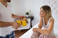 Young couple having having romantic times in bedroom. Young happy couple having having romantic times in bedroom Stock Image