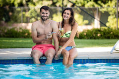 Young couple having iced tea at poolside Royalty Free Stock Images