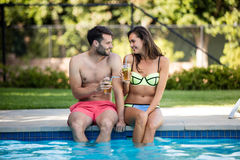 Young couple having iced tea at poolside Stock Photo