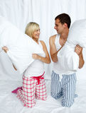 Young couple having a pillow fight Stock Photo