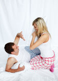 Young couple having a pillow fight Stock Image