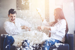 Young couple having pillow fight. Pillow fight. Young happy pregnant family have fun with fluffy feathers from pillow. Man and women dressed in jeans and white royalty free stock photo