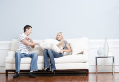 Young Couple Having a Pillow Fight on Sofa Stock Image