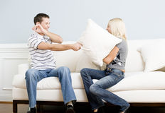 Young Couple Having a Pillow Fight on Sofa Stock Photos