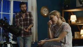 Young couple having quarrel at home. Young married man and woman in bedroom having conflict and arguing expressively while talking and shouting stock footage