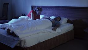 Young couple having relationship difficulties conflict. Woman confronts her husband on a bed in a night room. They have a conflict or he snores stock video footage