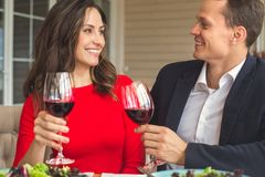 Young couple having romantic dinner in the restaurant cheers. Young men and women having romantic dinner in the restaurant holding wine glasses cheers laughing Royalty Free Stock Photo